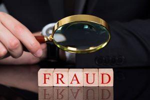 Fraud blocks through magnifying glass on desk